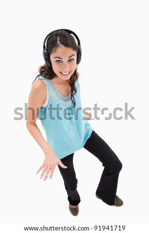 Portrait of a joyful woman dancing while listening to music against a white background