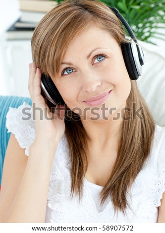 Portrait of a joyful woman listening to music with headphones in the living room