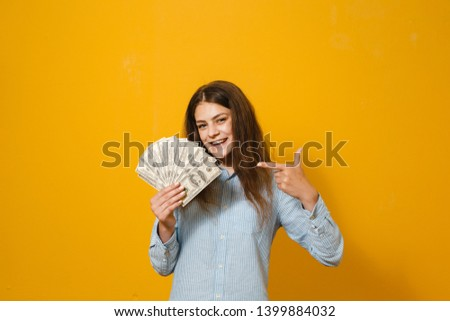 Portrait of a joyful woman showing dollars and showing gestures on a yellow background.
