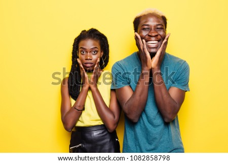 Portrait of a joyful young afro american couple screaming isolated over yellow