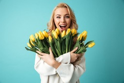 Portrait of a joyful young blonde woman in sweater holding yellow tulips bouquet isolated over blue background