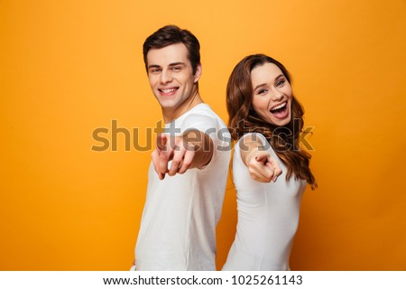 Portrait of a joyful young couple pointing fingers at camera isolated over yellow background