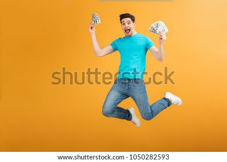 Portrait of a joyful young man in t-shirt holding bunch of money banknotes and celebrating while jumping isolated over yellow background