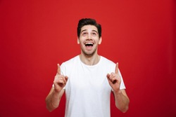 Portrait of a joyful young man in white t-shirt pointing fingers up at copy space isolated over red background