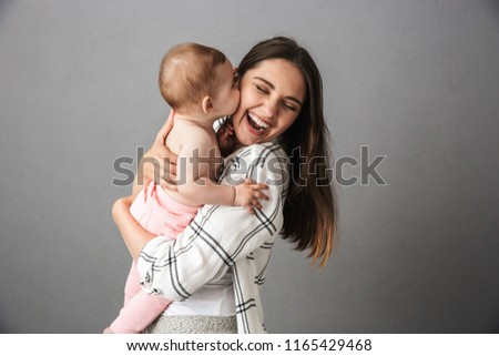 Portrait of a joyful young mother holding her little baby girl over gray background #1165429468