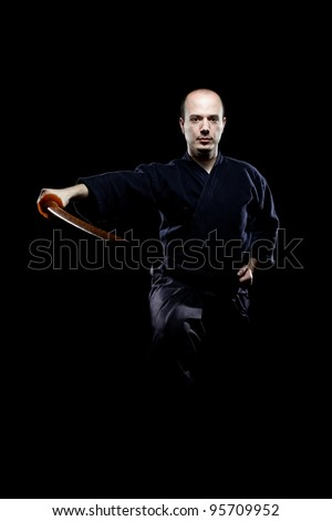 portrait of a kendo fighter with bokken, against black background