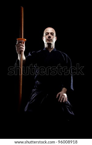 portrait of a kendo fighter with bokken, against black backgroung