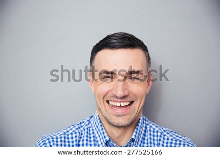 Portrait of a laughing man over gray background. Looking at camera - Shutterstock ID 277525166