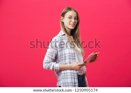 Portrait of a laughing woman using tablet computer isolated on a pink background and looking at camera #1250905174
