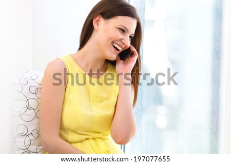 Portrait of a laughing young woman talking on mobile phone