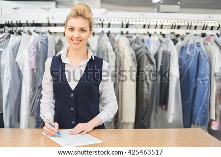 Portrait of a Laundry worker on the background of the clothing on hangers in dry cleaning