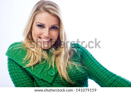 Portrait of a leaning blond woman smiling at camera wearing a green knitwear sweater on a white background