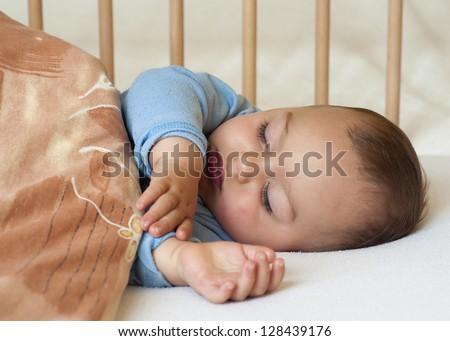 Portrait of a little baby boy sleeping under a blanket .