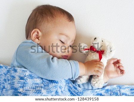 Portrait of a little baby boy sleeping under a blue blanket holding a white soft toy teddy bear.