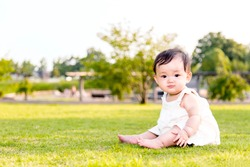 Portrait of a little baby girl seating and playing on green grass of park.
