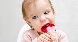 Portrait of a little baby with pink lollipop candy on a white background banner copy space. A child licks a heart-shaped candy. Harm to teeth
