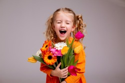 portrait of a little blonde girl with a bouquet of spring flowers on a light background. child in orange dress holding a bouquet of tulips in his hands. space for text. spring concept