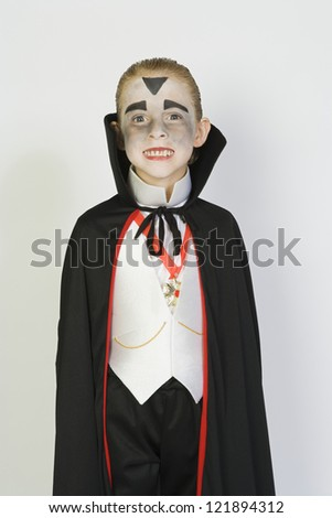 Portrait of a little boy dressed in vampire outfit isolated over white background