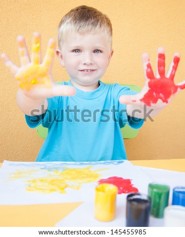 Portrait of a little boy enjoying his painting