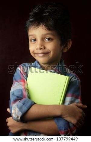 Portrait of a little boy holding a book