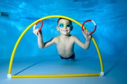 Portrait of a little boy in class underwater in a children's pool. He swims through the Hoop, pulls out toys. Active happy child. Healthy lifestyle. Swimming lessons under the water. A family sport