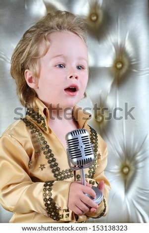 Portrait of a little boy in pop retro suit sings a song