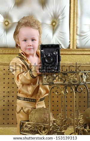 Portrait of a little boy in pop retro suit with old camera