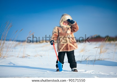 Portrait of a little boy on holiday standing on winter beach
