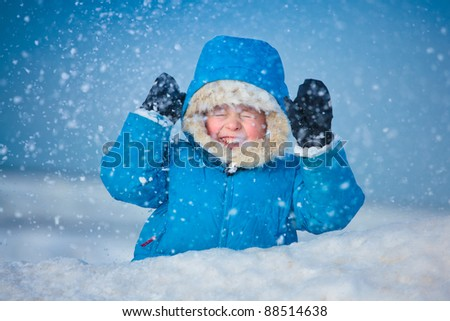 Portrait of a little boy playing outdoors in the snow