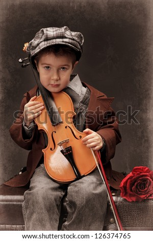 Portrait of a little boy sitting on a big old trunk with his violin. Retro style.