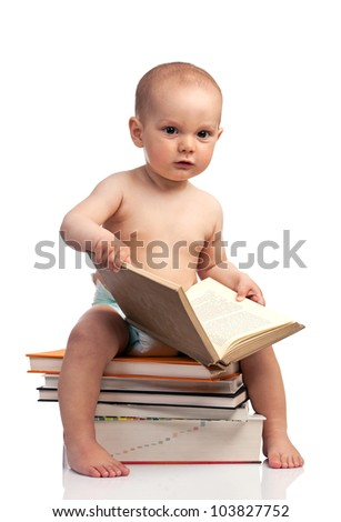 Portrait of a little boy sitting on a stack of books