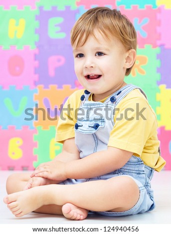 Portrait of a little boy sitting on floor - stock photo