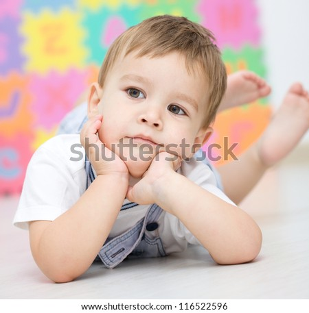 Portrait of a little boy who is laying on the floor