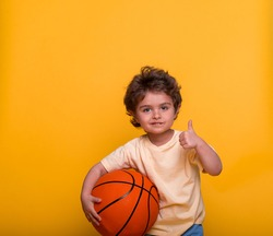 Portrait of a little boy with basketball isolated on yellow background. Small kid basketball player with thumb up. Sport child playing game. Kid activities. Little basketballer. Sports equipment