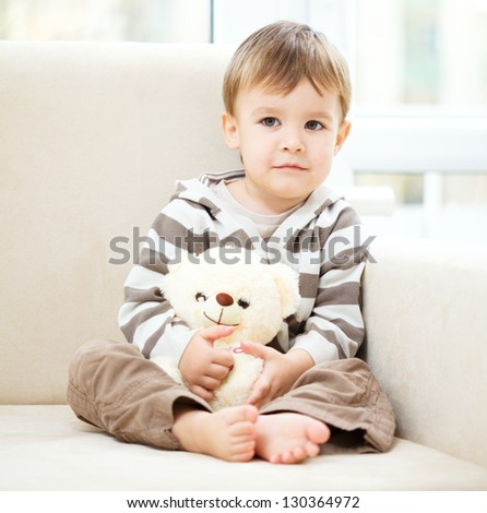 Portrait of a little boy with his teddy bear, indoor shoot