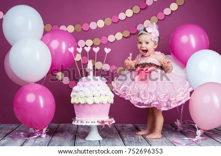 Photo of  Portrait of a little cheerful birthday girl with the first cake. Eating the first cake. Smash cake.