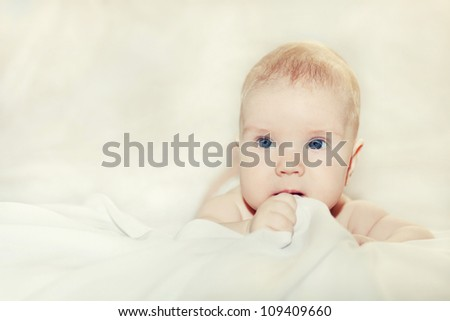 portrait of a little child lying on a blanket