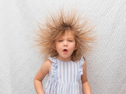 Portrait of a little coughing girl with electrified hair on a white background. Electricity power concept.