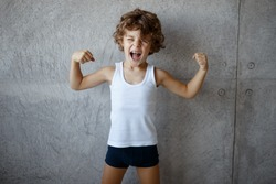 Portrait of a little curly haired red courageous boy in holding fists up and showing biceps on concrete grey background, with copy space.