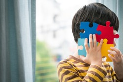 Portrait of a little cute Asian kid hold the colorful puzzles pieces to cover his face. World autism awareness day, Mental health care, Child development, Autism Spectrum Disorder concept.