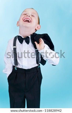 Portrait of a little funny boy in black suit