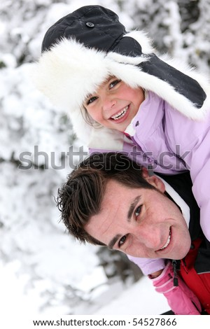 Portrait of a little girl and a man at the snow