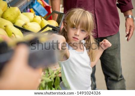 Portrait of a little girl buys fruit
