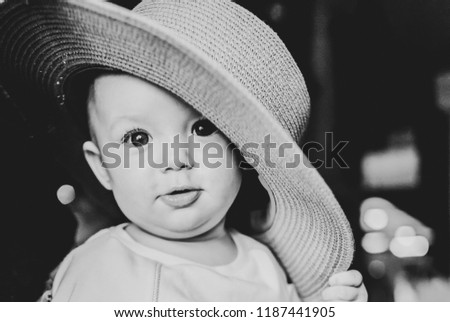 portrait of a little girl (child) with a large straw hat on her head smiling and posing for a camera in a cafe on her mother's hands. black and white