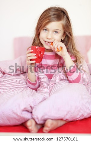 Portrait of a little girl eating healthy meal on the bed in her bedroom