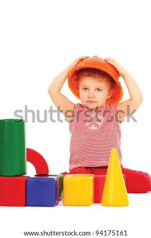 Portrait of a little girl in a helmet with blocks