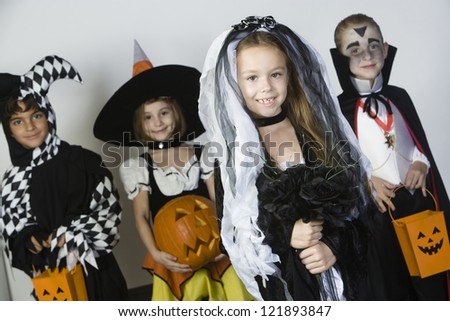 Portrait of a little girl in Halloween outfit with friends holding pumpkin in the background