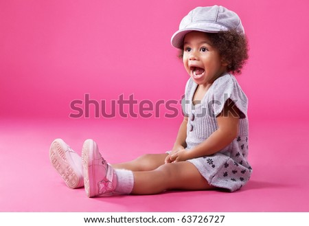 stock photo : Portrait of a little girl in stylish clothing sitting on pink background and playing up