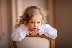 Portrait of a little girl in the studio. A girl in a dress and with blond curly hair. Girl sitting on a chair. Image with selective focus.