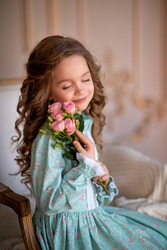Portrait of a little girl in the studio. A girl sits in a chair and holds a bouquet of roses in her hands. Image with selective focus.